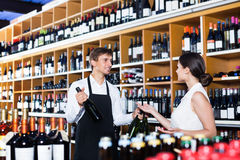 Seller helping woman customer with bottle of wine. Young men seller wearing uniform helping women customer with the bottle of wine at wine house Stock Images