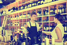 Seller helping woman customer with bottle of wine. Young men seller wearing uniform helping women customer with the bottle of wine at a wine house Royalty Free Stock Photos
