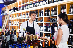 Seller helping woman customer with bottle of wine. Young men seller wearing uniform helping women customer with a bottle of wine at wine house stock photos