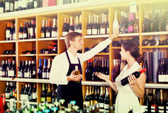 Seller helping woman customer with bottle of wine. Young men seller wearing uniform helping women customer with bottle of wine in the wine house Stock Image