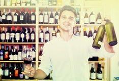 Seller holding bottle of wine Stock Photography