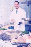 Seller holding fish Stock Photos