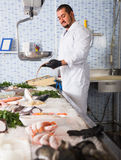 Seller holding fish Royalty Free Stock Image