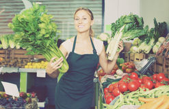 Seller holding fresh celery and mangold Royalty Free Stock Images