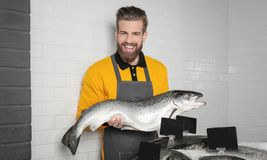 Seller holding fresh fish. In supermarket Royalty Free Stock Photography