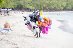Seller of inflatable toys and swimming laps goes along the beach in island Mauritius. GRAND BAY, MAURITIUS - MARCH 07, 2017 : Unknown seller of inflatable toys Royalty Free Stock Image