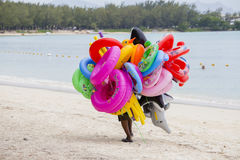 Seller of inflatable toys and swimming laps goes along the beach in island Mauritius Royalty Free Stock Photos