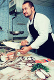 Seller with knife cut fish Stock Image