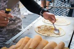 Seller making Khanom Tokyo thin flat pancake Thai street snack Stock Photography