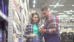 Seller man in plaid shirt advises girl in shop stock footage