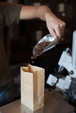 Seller man pour coffee beans in a paper bag. Weighs and sells in the coffee shop Stock Photo