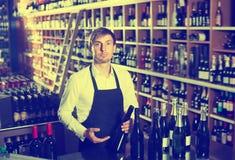 Seller man promoting bottle of wine. Seller man wearing apron promoting bottle of wine in wine store Stock Photography