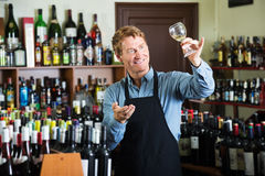 Seller man in wine store. Positive male seller wearing apron suggesting to taste glass of wine in store royalty free stock image