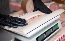 The seller in the market with gloves wraps sliced sausage on the scales royalty free stock photography