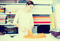 Seller measuring cloth. Female shop assistant measuring piece of cloth at drapery shop Royalty Free Stock Images