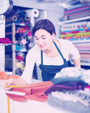 Seller measuring cloth. Female shop assistant measuring piece of cloth at drapery shop Royalty Free Stock Photos