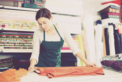 Seller measuring cloth. Smiling girl seller taking measurement of cloth at drapery shop Royalty Free Stock Images