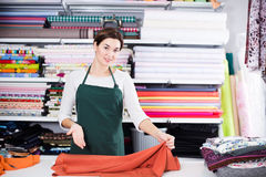Seller measuring cloth. Smiling girl seller taking measurement of cloth at drapery shop Royalty Free Stock Photography