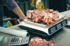 Raw meat on the scales. The seller of meat weighs fresh beef meat on scales Stock Photos