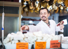 Seller offering displayed sorts of meat Royalty Free Stock Photo