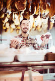 Seller offering displayed sorts of meat Stock Photography