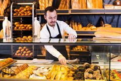 Seller offering fresh tasty bun. Positive young male seller offering fresh tasty bun in bakery royalty free stock images
