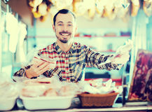 Seller offering sorts of meat Royalty Free Stock Image