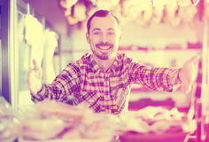 Seller offering sorts of meat Royalty Free Stock Photo
