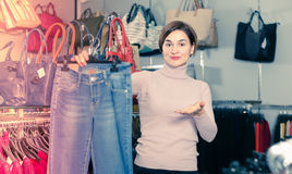 Seller offers the option of jeans. The seller offers the option of jeans in a clothing store Royalty Free Stock Image