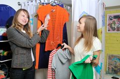 Seller offers to a girl a blouse. Seller offers to girl a blouse Royalty Free Stock Photo