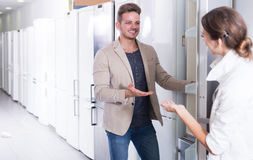 Seller offers to a happy  woman help to buy fridge Stock Image