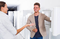 Seller offers to a smiling woman help to buy fridge Royalty Free Stock Image