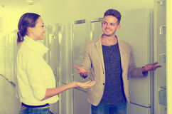Seller offers to a smiling woman help to buy fridge Stock Photography