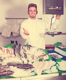 Seller posing near cooled fish Royalty Free Stock Photos