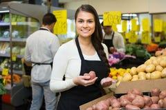 Seller with potato in market. Smiling seller with potato in market, prices are on Spanish stock photo