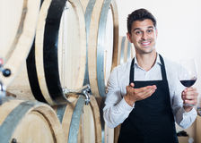 Seller pouring wine in cellar Stock Photo