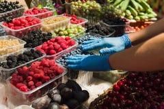 Seller preparing organic fresh berries at market. Royalty Free Stock Photography