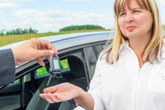 seller presents the woman key from the new car stock photo