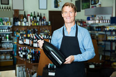 Seller promoting bottle of wine. Cheerful seller man in apron promoting bottle of wine in wine store Stock Image