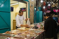 The seller sells sweets to the customer on the market in the old town of Acre in Israel. Acre, Israel, November 03, 2017 : The seller sells sweets to the Stock Photo