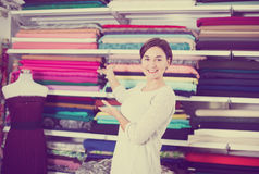 Seller showing assortment. Female shop assistant demonstrating assortment at drapery shop Royalty Free Stock Photos