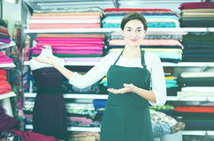 Seller showing assortment. Female shop assistant demonstrating assortment at drapery shop Royalty Free Stock Photography
