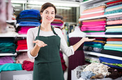 Seller showing assortment. Smiling girl seller showing wide assortment at drapery shop Royalty Free Stock Photo