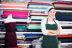 Seller showing assortment. Smiling girl seller showing wide assortment at drapery shop Royalty Free Stock Photography