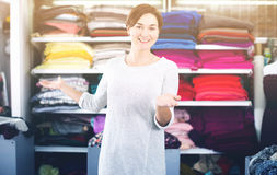 Seller showing assortment. Young woman seller displaying various fabrics at drapery shop Royalty Free Stock Photography