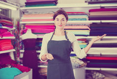 Seller showing assortment. Young woman seller displaying various fabrics at drapery shop Stock Photography