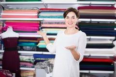 Seller showing assortment. Young woman seller displaying various fabrics at drapery shop Stock Photos