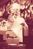 Seller showing piece of meat in butcher's store. Smiling male seller showing piece of meat in butcher's store Royalty Free Stock Image