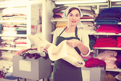 Seller showing white fabric. Female shop assistant demonstrating white fabric at drapery shop Stock Images