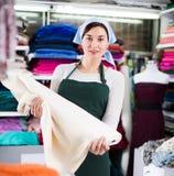 Seller showing white fabric. Smiling girl seller showing white fabric at drapery shop Royalty Free Stock Photo